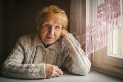 Elderly woman sitting at a loss. Stock Images