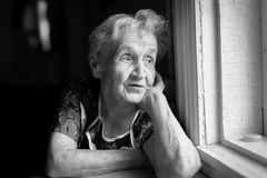 An elderly woman sitting near the window. Royalty Free Stock Photos