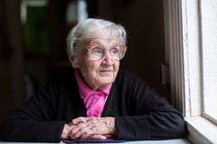 An elderly woman sitting near the window. Portrait. Stock Images