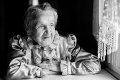 An elderly woman sitting near the window. Royalty Free Stock Image
