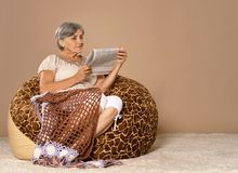 Elderly woman sitting with newspaper Stock Photos