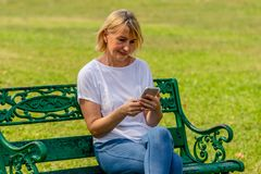 Elderly Woman Sitting On Bench And Using Her Mobile Phone To Text Message Stock Photo