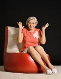 Elderly woman sitting on red armchair Stock Image