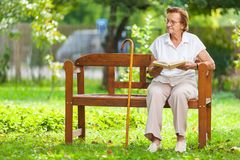 Elderly woman sitting and relaxing on a bench in park stock photography