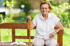 Elderly woman sitting and relaxing on a bench in park stock photos