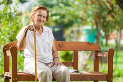 Elderly woman sitting and relaxing on a bench in park royalty free stock images