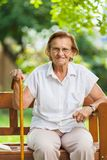 Elderly woman sitting and relaxing on a bench in park. Elderly woman sitting and relaxing on a bench outdoors in park royalty free stock photography