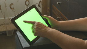 Elderly woman sitting on sofa at home and using a digital tablet pc with green screen, back view. Tablet PC in a adult. Woman hands stock video footage