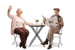 Elderly woman sitting at a table with a cup of coffee and waving and an elderly man reading a newspaper stock images