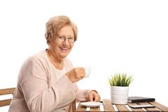 Elderly woman sitting at a table drinking coffee royalty free stock images