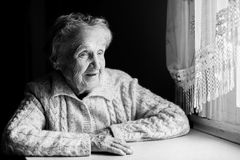 Elderly woman sitting at a table near the window. Royalty Free Stock Photo