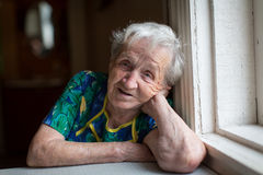 Elderly woman sitting at the table. Royalty Free Stock Images