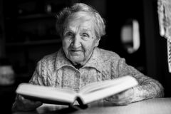 Elderly woman sitting at a table reading a book. Royalty Free Stock Photography