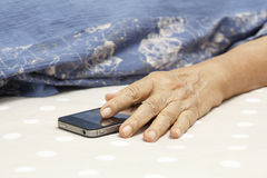 Elderly woman sleeping and holding a mobile phone. Stock Photos