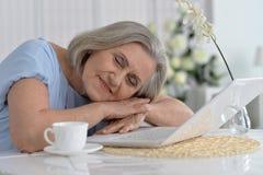 Elderly woman sleeping near  laptop Stock Images