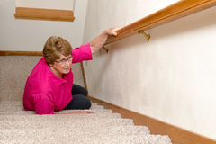 Elderly Woman Slip Fall Home Accident. An old mature senior elderly woman has had a slip and fall on a stairway. The stairs are a mobility issue and she fell in stock images