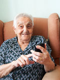 Elderly woman with a smart phone and smiling Royalty Free Stock Photo