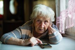 An elderly woman with a smartphone sitting at the table.  Training. Royalty Free Stock Image