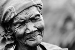 An elderly woman smiles with sadness and modesty in Gulu, Uganda royalty free stock image