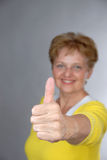 Elderly woman smiles with thumb up Royalty Free Stock Photos