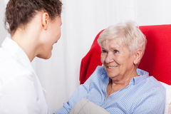 Elderly woman smiles to nurses Royalty Free Stock Images