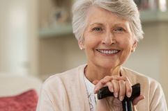 Elderly woman smiling at home. Retired woman with her wooden walking stick at home. Happy senior woman relaxing at home holding cane and looking at camera royalty free stock images