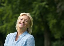 Elderly woman smiling outdoors Stock Photos