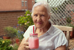 Elderly woman with smoothie. Portrait of the smiling elderly woman, sitting in a garden with glass of strawberry smoothie Stock Photography