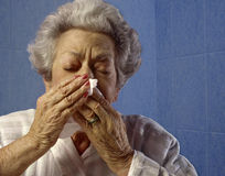 Elderly woman sneezing Stock Photo