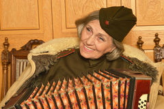 Elderly woman solder playing accordion closeup Stock Images