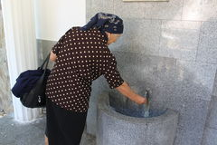 Elderly woman at source. Water to treat eye diseases at Baile Herculane,Romania Stock Images