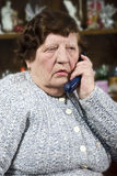 Elderly woman speaking at phone royalty free stock photography