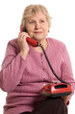 The elderly woman speaks on the phone. On white stock photography