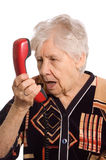 The elderly woman speaks on the phone. On white stock photos