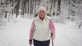 The elderly woman spends leisure-time in the wood. Winter forest. The woman supports the level of physical activity. The stock video