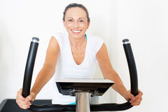 Elderly woman during spinning exercise stock images
