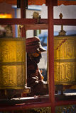 Elderly woman spinns prayer wheels in The Palkhor Monastery Gyan Stock Images