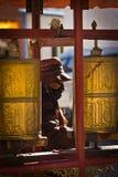 Elderly woman spinns prayer wheels in The Palkhor Monastery Gyan Stock Images