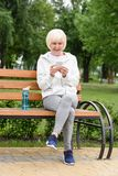 Elderly woman in sportswear using smartphone while sitting on bench with sport bottle. Of water royalty free stock photography