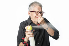 Elderly woman spraying air refreshener. Disgusted by horrid smell senior caucasian woman is spraying air freshener Stock Images