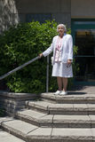 Elderly woman on stairs. Outdoor stock photography