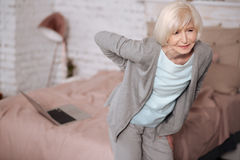 Elderly woman standing with backache Stock Photos