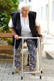 Elderly woman standing with her walker Royalty Free Stock Photos