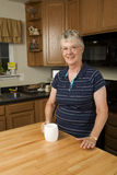 Elderly woman standing in kitchen Royalty Free Stock Image