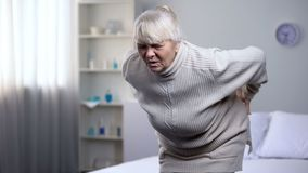 Elderly woman standing up from bed and suddenly feeling lower back pain, health royalty free stock images