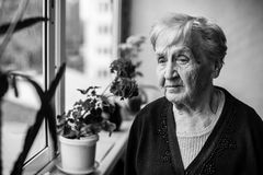An elderly woman stands on the balcony Royalty Free Stock Images