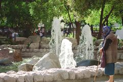 An elderly woman stands near a fountain on Chistoprudny Boulevard in Moscow. stock images