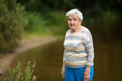An elderly woman stands in the Park near the pond. Nature. Royalty Free Stock Photos