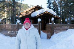 Elderly woman stands and smiles happily in front of a rustic wooden house among the snowdrifts in the forest. Winter. Elderly woman stands and smiles happily in stock photo