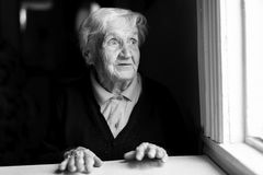 An elderly woman stares out of the window. Black and white photo Stock Photo